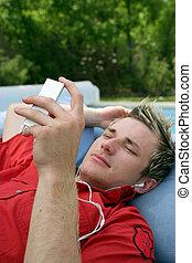 Man laying in garden listening to music