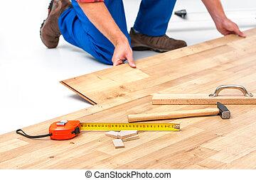 Man laying laminate flooring - carpenter worker installing...
