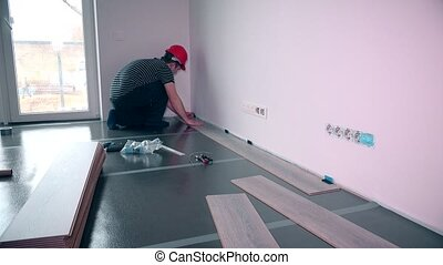 Man laying laminate flooring in construction. Static shot....