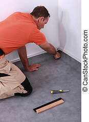 Man laying new carpet in home