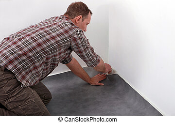 Man laying new carpet in room