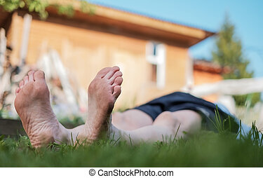 Man laying on grass field. He relax on nature in summer.