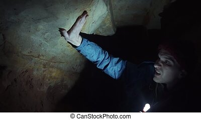 Man laying on ground into narrow cave explores cave walls...