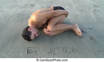 Man laying on the beach near the water in embryo pose. ...