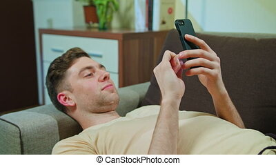 Man Laying on the Sofa and Using Mobile Phone - Man Laying...