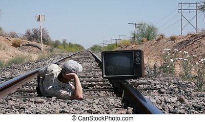 Man laying on the railway tracks with an old, retro TV.