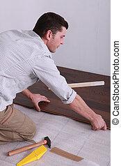 Man laying parquet flooring