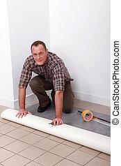 Man laying pvc flooring