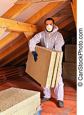 Man laying thermal insulation layer under the roof - carry...