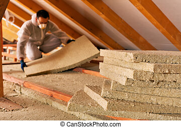 Man laying thermal insulation layer under the roof - Man...
