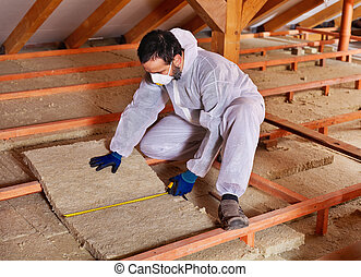 Man laying thermal insulation layer under the roof -...