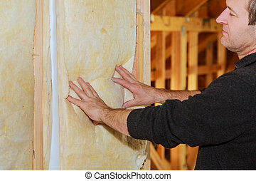 Man laying thermal insulation layer under the roof - using...