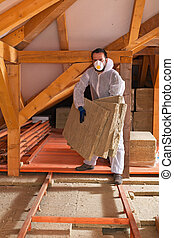 Man laying thermal insulation layer under the roof
