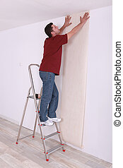 Man laying wall paper