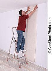 Man laying wall paper