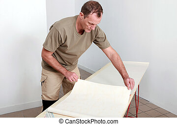 Man laying wallpaper