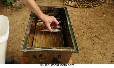 man lays fresh fish perch on the grill smokehouse