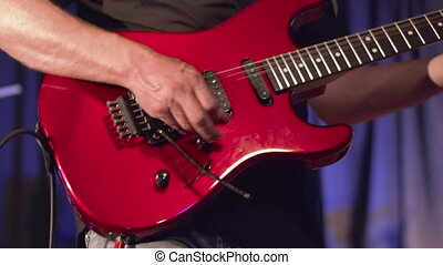 Man lead guitarist playing electrical guitar on concert stage .
