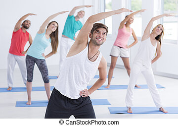 Man leading the pilates training for group of young people