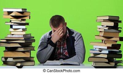 Man leafing through a textbook, it suffers from headaches....