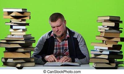 Man leafing through a textbook, suffers from headaches....