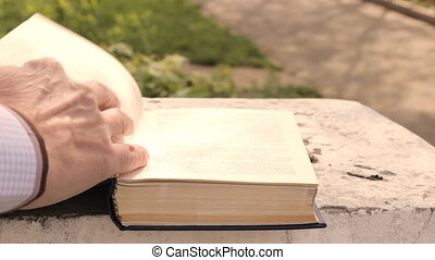 Man leafing through pages of a book, close-up