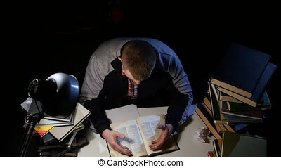 Man leafing through the book and could not find what he is looking for rastroilas and angry. Black background. View from above
