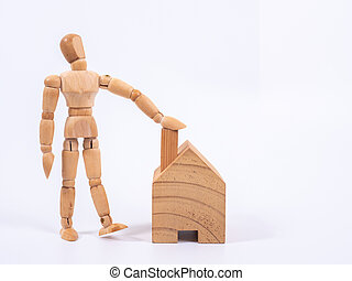 Man leaned against the model of a house isolated on white background. Concept with a wooden puppet