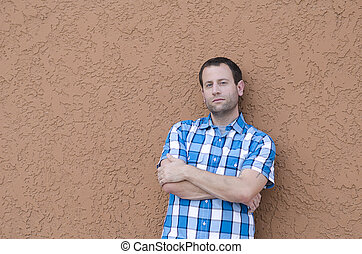 Man leaning against a wall with his arms crossed.