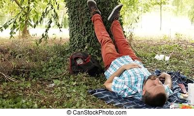 Man Leaning Feet against Tree