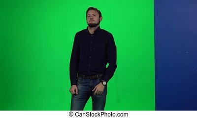 Man leaning hand on wall standing against chroma key...