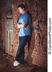 Man leaning on a brick wal