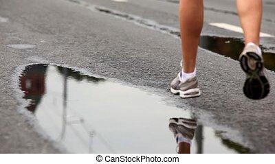 Man legs in trainers run on wet asphalt