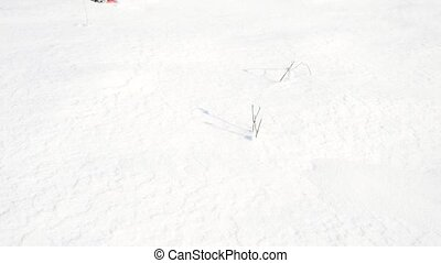 Man legs with snowshoes walk in snow. Detail of winter hike in snowdrift, snowshoeing with trekking poles and shoe cover in powder snow. Gentle wind brings small snow flakes