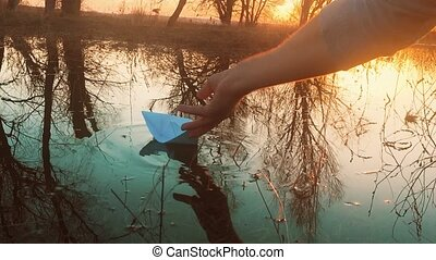 man lets a paper boat into the water. childhood is a memory...