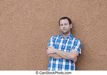man, leunende tegen een muur, met, zijn, armen, crossed.