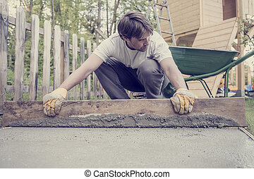 Man leveling the cement in a backyard