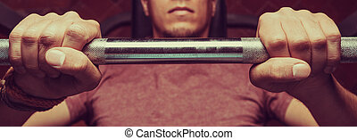 Man lifting a barbell - Muscular man lifting a barbell on...