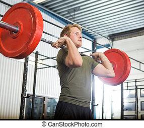 Man Lifting Barbell At Gym - Fit young man lifting barbell...
