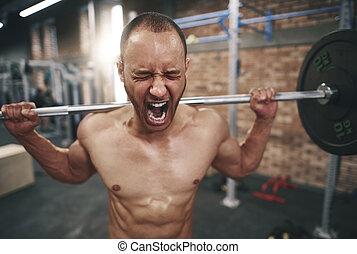 Man lifting barbell in health club