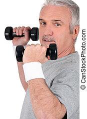 Man lifting dumbbells at the gym