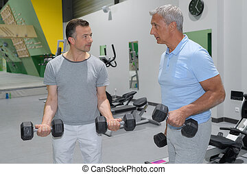 man lifting dumbbells in gym