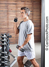 Man Lifting Dumbbells In Health Center - Young man lifting...