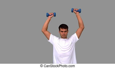 Man lifting dumbbells on grey screen in slow motion