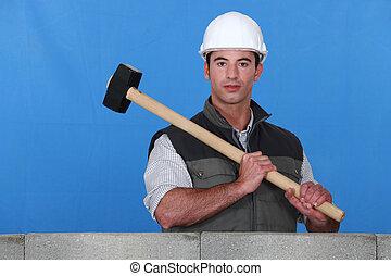 Man lifting hammer next to wall