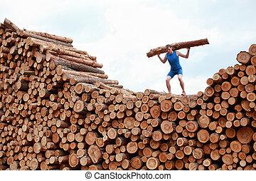 man lifting heavy log - training - man on top of large pile...