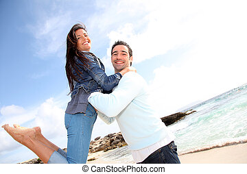 Man lifting his girlfriend up in arms by the beach