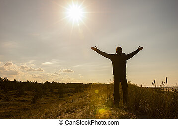Man lifting his hands up silhouette background