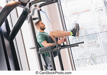 Man lifting his legs up on a gym machinery