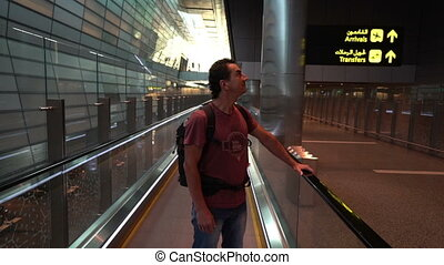 man lifting on escalator at airport terminal, passenger looking around excited, travel concept, inspirational people, positive attitude